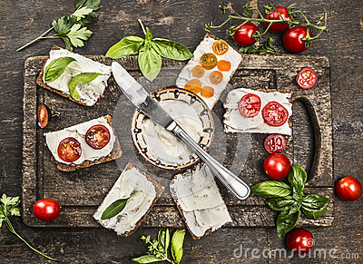 Slice of fresh rye bread with cream cheese with basil and tomatoes on vintage wooden cutting board, viewed from above