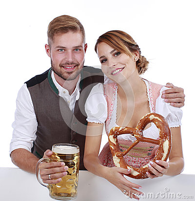 Bavarian couple in traditional costume with beer and brezel