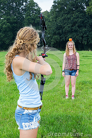 Girl aiming arrow of compound bow at apple on head of woman