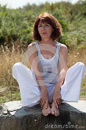 Sad mature yoga woman siting on a stone outdoors