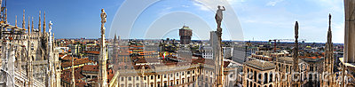 HDR panorama photo of white marble statues of Cathedral Duomo di Milano on piazza, Milan cityscape and the Royal Palace of Milan
