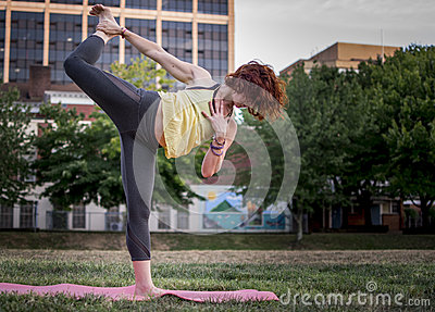 Pretty Young Woman Practicing Yoga in the Park