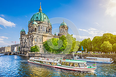 Berlin Cathedral with boat on Spree river at sunset, Germany