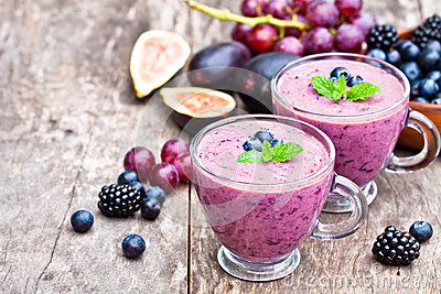 Fresh healthy pulpy cocktail with purple fruits and berries