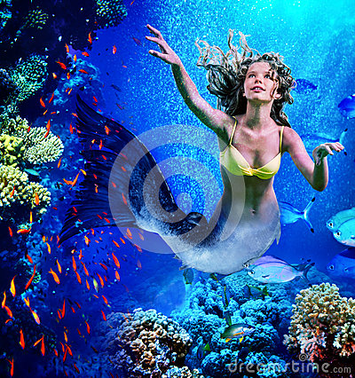 Mermaid dive underwater through coral