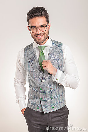 Business man wearing white shirt, grey vest and green tie.
