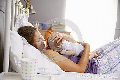 Mother In Bed Holding Sleeping Newborn Baby Daughter