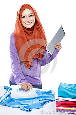 Young woman wearing hijab reading article on tablet while ironin