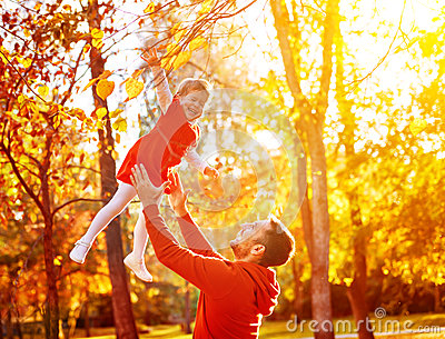 Happy family Dad throws child daughter up on walk in autumn