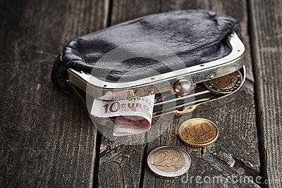 Purse with money on wooden table