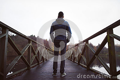 Man on wooden bridge over a lake, on a damp autumn day.