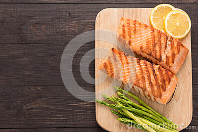 Grilled salmon and lemon, asparagus on the wooden background