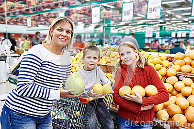 Mother and children with pineapples in fruit department in super