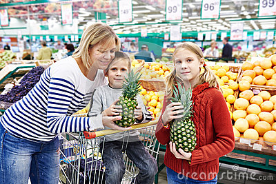 Mother and children with pineapples in fruit department of super