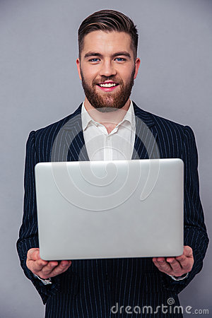 Portrait of a happy businessman holding laptop