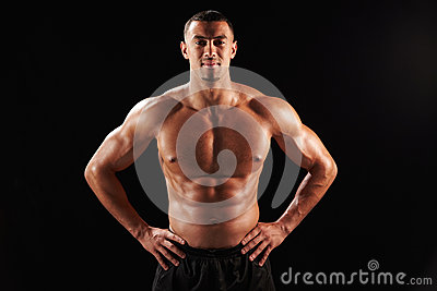 Smiling bare chested male body builder with hands on hips