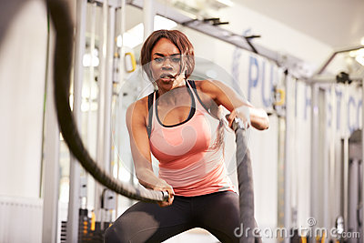 Young woman working out with battle ropes at a gym