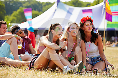 Friends sitting on grass  watching a gig at a music festival