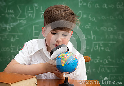 Schoolboy with globe and  loupe