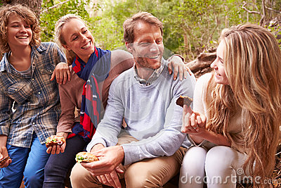 Parents and teenage kids eating outdoors in a forest