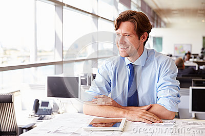 Male architect at his desk in an office, looking away