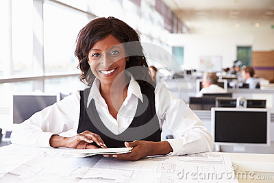 Young female architect working at desk, looking to camera