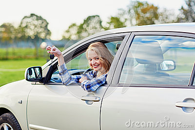 Beautiful young driver looking out of the car holding key