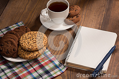 Stilllife with a notebook and cookies on the wooden table