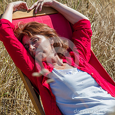 Relaxed 50s woman enjoying sun warmth on her deckchair