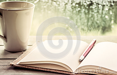 Pen on open notebook and coffee cup