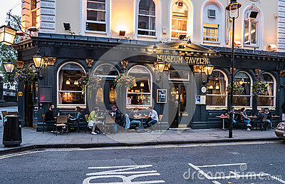 Patrons socialize at tables outside Museum Tavern, London