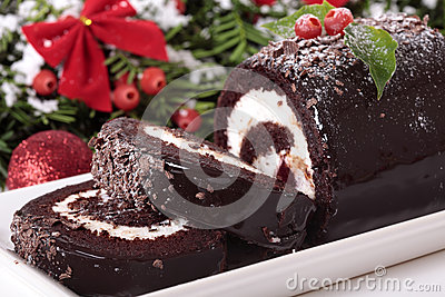 Slice of Christmas yule log cake on plate with decoration