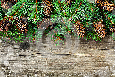 Christmas decoration of fir tree and conifer cone on textured wood background, magic snow effect