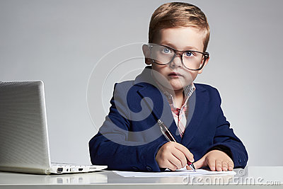 Business boy. funny child in glasses writing pen. little boss in office