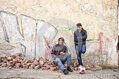 Two street hooligans standing against a graffiti pain