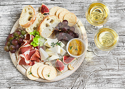 Delicious appetizer to wine - ham, cheese, grapes, crackers, figs, nuts, jam, served on a light wooden board, and two glasses with
