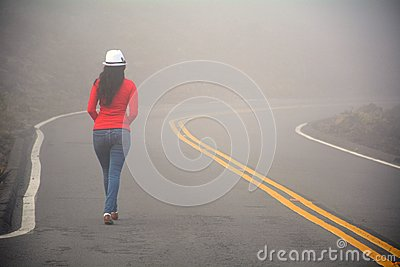 Woman walking alone on the road in the fog