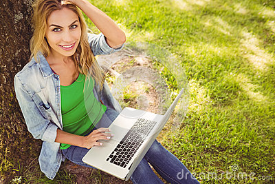 High angle portrait of woman holding laptop with hand in hair