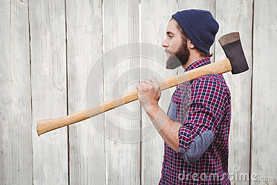 Side view of hipster with axe on shoulder