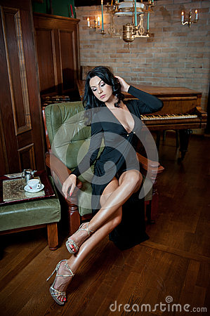 Beautiful sexy girl sitting on chair and relaxing. Portrait of brunette woman with long legs posing challenging. Sensual female