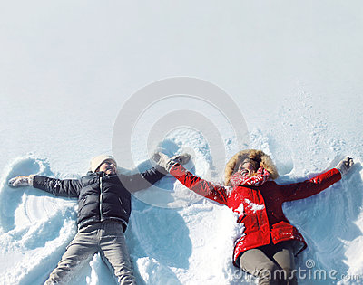 Happy mother and son playing having fun together lying in snow winter