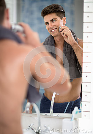 Reflection of man in mirror shaving with electric shaver