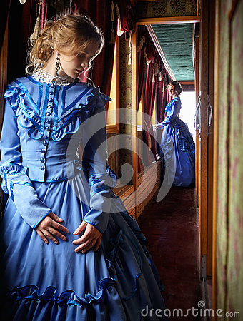 Young woman in blue vintage dress standing in corridor of retro