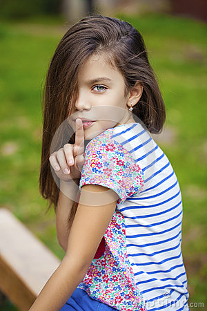 Little girl has put forefinger to lips as sign of silence for Beautiful small teen