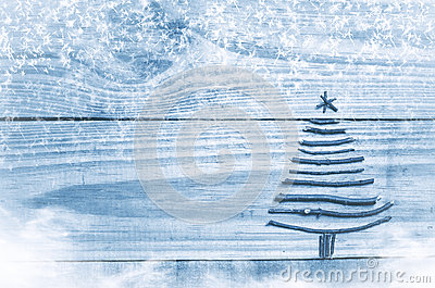Christmas tree made from dry sticks on wooden, blue background. Snow and snow flaks image. Christmas tree ornament with star.