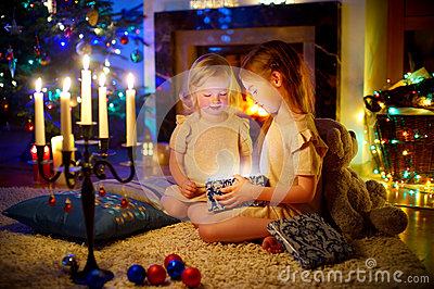 Adorable little girls opening a magical Christmas gift