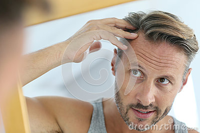 Mirror portrait of man concerned by hair loss