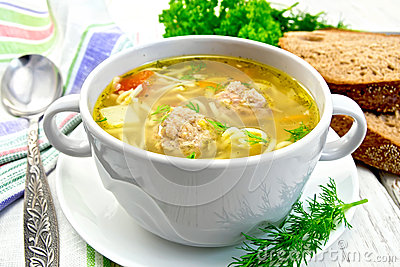 Soup with meatballs and noodles in bowl on saucer