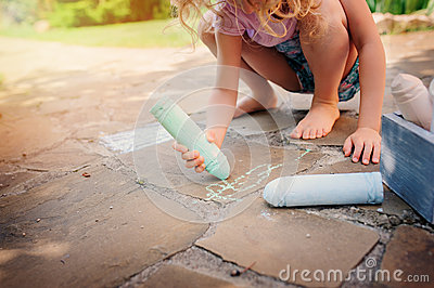 Child girl drawing with chalks in summer