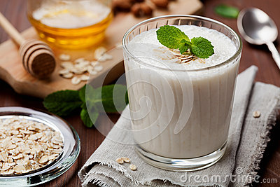 Healthy breakfast of banana smoothie or milkshake with oats and honey decorated mint leaves